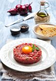 Raw Steak tartar with egg yolk, red onion, capers, spicy sauce, sea salt, pepper and olive oil. Royalty Free Stock Photography