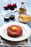 Raw Steak tartar with egg yolk, red onion, capers, spicy sauce, sea salt, pepper and olive oil. Stock Photo