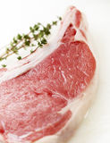 Raw steak with thyme on a white cutting board. Raw steak on a white cutting board with thyme Stock Images