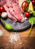 Raw steak turkey in a pan with onions tomatoes garlic on a branch greens on a rustic wooden background close up Stock Images