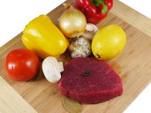 Raw steak. With vegetable on wooden board Royalty Free Stock Images