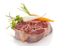 Raw steak with vegetables. Raw veal shank meat with fresh vegetables on white. Ossobucco cooking Royalty Free Stock Photo