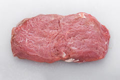 Raw steak on a white board Royalty Free Stock Images