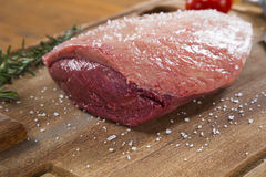 Raw steak on wooden board. With tomato Stock Photos