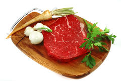 Raw steak on wooden board and vegetables Stock Photography