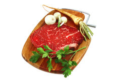 Raw steak on wooden board and vegetables Stock Image