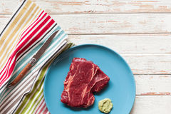 Raw steak on wooden table Stock Photography