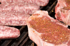 Raw steaks and bratwurst Stock Photography