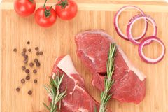 Raw steaks on cutting board. Royalty Free Stock Photo