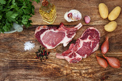 Raw steaks with ingredients for grilling. Raw steaks with spices and ingredients for grilling on a rustic wooden board Stock Photography