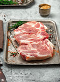 Raw steaks on iron tray on light surface Stock Images