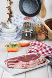 Raw steaks on the kitchen table. Ready to cook Royalty Free Stock Photography