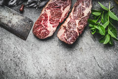 Raw steaks with meat cleaver and fresh condiment on dark rustic concrete background , top view, border. Dry aged raw beef steaks Stock Photo
