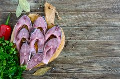 Raw steaks river fish on a wooden cutting board on a table. Carp ready for cooking. Top view stock photography