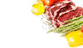 Raw steaks and vegetables Stock Photo