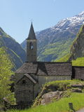 Raw stone,mountain church. Cute, little church built from raw stone standing amidst fresh spring green in a mountain valley in Ticino,Switzerland Stock Image