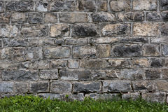 Raw stone wall background and green grass. Stock Photo