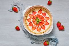 Raw strawberry tart on the gray kitchen background. Berries cheesecake decorated with organic fresh strawberries and mint. Delicious healthy summer dessert stock photography