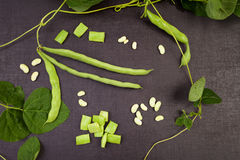 Raw string beans. Raw green string beans, whole and sliced, black surface. Healthy legumes eating Stock Photo