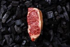 Raw Striploin steak on charcoal. Raw fresh meat Striploin steak on black charcoal background Stock Photo
