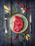 Raw Striploin Steak on  plate with  knife and fork. To lay with herbs and spices, blue wooden background, top view Stock Images