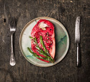 Raw Striploin Steak on  plate with rosemary, garlic, salt and pepper on dark wooden background Stock Photos
