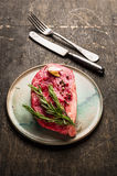 Raw Striploin Steak preparation with herbs and spices on old wooden Stock Image
