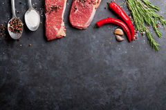 Raw striploin steak. With rosemary, salt and pepper cooking over stone table. Top view with copy space Royalty Free Stock Image