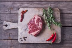 Raw striploin steak with rosemary, salt and pepper on the wooden board. Top view.  Stock Photos