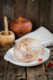 Raw stuffed chicken roll with spice ready to roast in white bowl on wooden background. Selective focus Royalty Free Stock Photo
