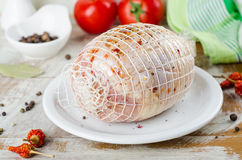 Raw stuffed chicken roll with spice ready to roast in white bowl on wooden background. Selective focus Stock Photos