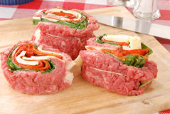 Raw stuffed flank steak. Raw flank steak stuffed with swiss cheese, red peppers, and spinach being prepared royalty free stock photo