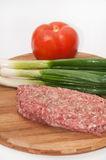 Raw stuffed hamburger on wooden board with tomatoes and onions.  Royalty Free Stock Images