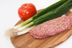 Raw stuffed hamburger on wooden board with tomatoes and onions.  Stock Photography