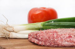 Raw stuffed hamburger on wooden board with tomatoes and onions.  Royalty Free Stock Image