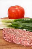 Raw stuffed hamburger on wooden board with tomatoes and onions.  Stock Photos