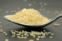 Raw Sugar. Macro shot of raw sugar in a teaspoon on a black plate Royalty Free Stock Photos