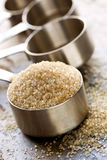 Raw Sugar in Measuring Spoon. Raw sugar overflowing a measuring spoon, over slate background stock photos