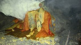 Raw sulfur mining in the crater of Kawah Ijen active volcano on Java stock image