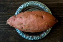Raw sweet potatoes on metal plate over wooden table. Royalty Free Stock Photo
