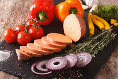 Raw sweet potatoes, peppers, tomatoes, onions, garlic, rosemary. And spices close-up on the table. horizontal Stock Image
