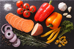 Raw sweet potatoes, peppers, tomatoes, onions, garlic, rosemary. And spices close-up on the table. horizontal view from above Royalty Free Stock Images