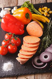 Raw sweet potatoes, peppers, tomatoes, onions, garlic, rosemary. And spices close-up on the table. Vertical Stock Image