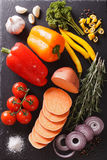 Raw sweet potatoes, peppers, tomatoes, onions, garlic, rosemary. And spices close-up on the table. vertical view from above Royalty Free Stock Photos