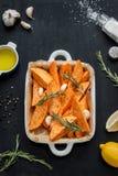 Raw sweet potatoes prepared to bake in white ceramic roasting dish Royalty Free Stock Photo