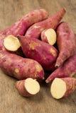Raw sweet potatoes on wooden background closeup. Batata doce fresca sobre uma madeira royalty free stock images