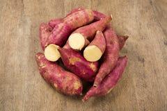Raw sweet potatoes on wooden background closeup. Batata doce fresca sobre uma madeira royalty free stock photo