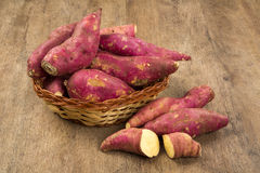Raw sweet potatoes on wooden background closeup Royalty Free Stock Images