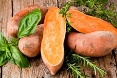 Raw sweet potatoes on wooden background closeup royalty free stock photos