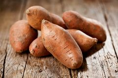 Raw sweet potatoes on wooden background closeup. stock images